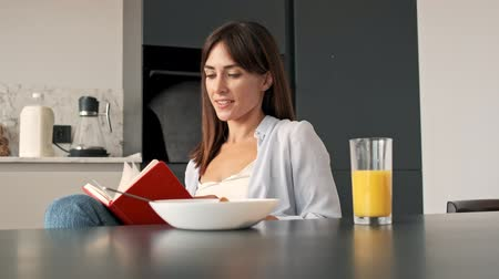 flocos de milho : Beautiful calm young woman writing in notebook while having a breakfast sitting at kitchen in the morning Stock Footage