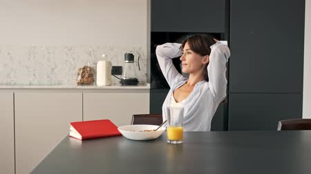 flat head : Side view of cheerful young woman sitting with hands behind her head and looking at the window while having breakfast at kitchen in the morning Stock Footage