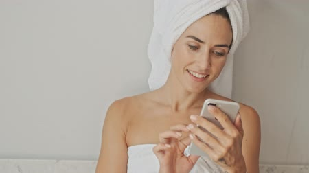 toalha : Charming young woman wearing white towel after bath and using smartphone while relaxing at home in the morning