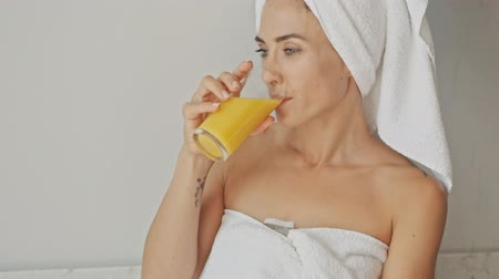 toalha : Cheerful thoughtful young woman wearing white towel after bath and drinking orange juice while relaxing at home in the morning