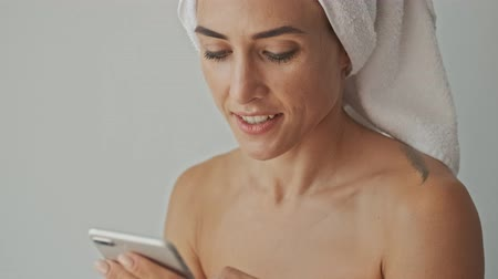 close cropped : Cropped view of happy young woman in white towel smiling and using smartphone while relaxing after bath at home in the morning