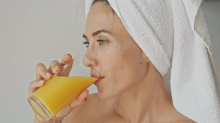 flat head : Attractive pleased young woman with white towel on her head smiling and drinking orange juice while relaxing after bath at home in the morning Stock Footage