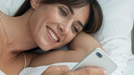 закрытыми глазами : Close up view of attractive cheerful young brunette woman closing her eyes and falling asleep while using smartphone lying in the bed Стоковые видеозаписи