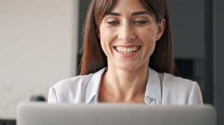 escritor : Charming cute young business woman smiling and working on laptop while sitting at the table Stock Footage
