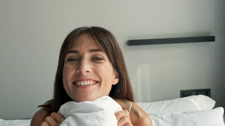 pajama : Cheerful pretty young brunette woman smiling and closing her face with blanket while sitting in bed in the morning Stock Footage
