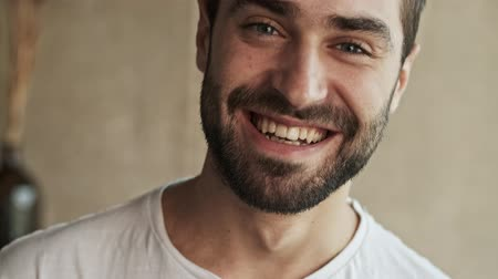 flat head : Close up view of beautiful cheerful young brunet man smiling and laughing while looking at the camera at home