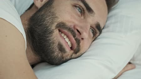 acorde : Close up view of handsome happy young brunet man smiling and relaxing while lying in bed in the morning