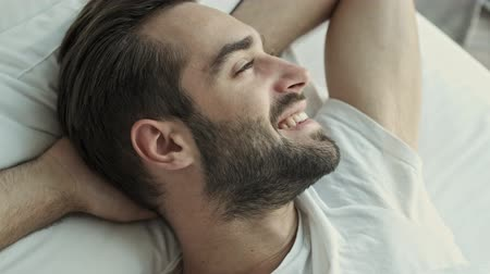 flat head : Close up view of cheerful thoughtful young brunet man smiling and looking to the side while lying with hands behind his head in bed in the morning Stock Footage