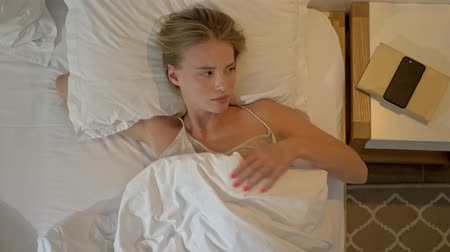 gadżety : Top view of attractive young blonde woman sleeping while lying in bed at home Wideo