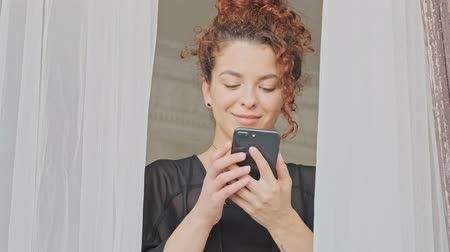 kurtyna : Cheerful beautiful young redhead woman in silk robe having a call on smartphone while looking at the window at home in the morning