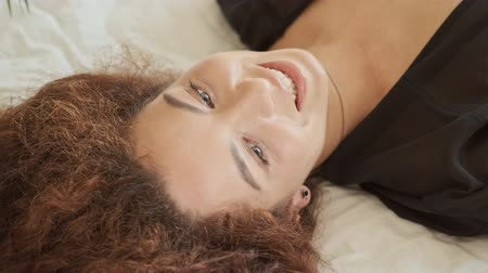 close cropped : Cropped view of attractive cheerful young redhead woman in silk robe smiling and laughing while lying in bed at home in the morning Stock Footage