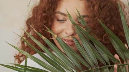 shy girl : Close up view of charming young redhead woman in white shirt smiling and touching home plant while looking through it to the side