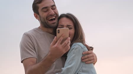 adorável : Happy charming young lovely couple smiling and laughing while using smartphone outdoors