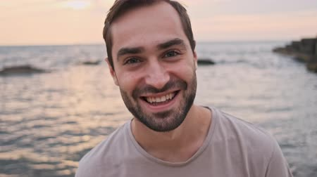 rejoice : Close up view of handsome cheerful young bearded man smiling and fixing his hair with hand while relaxing near the sea
