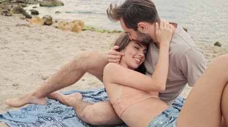 закрытыми глазами : Handsome calm young bearded man hugging with his cute young girlfriend and kissing her in forehead while lying on plaid near the ocean Стоковые видеозаписи