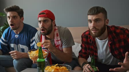 watch tv : Three shocked men fans worried and screaming while drinking beer and watching sport at apartment Stock Footage