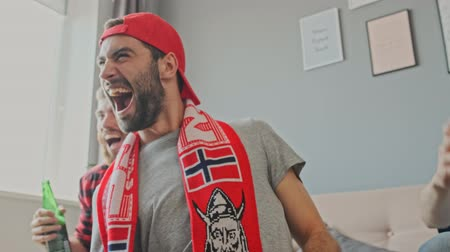 watch tv : Happy bearded male fan wearing in cap rejoicing and screaming while sitting together with friends and watching sport at apartment