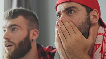 поражение : Two surprised bearded male fans getting shock while watching sport at apartment Стоковые видеозаписи