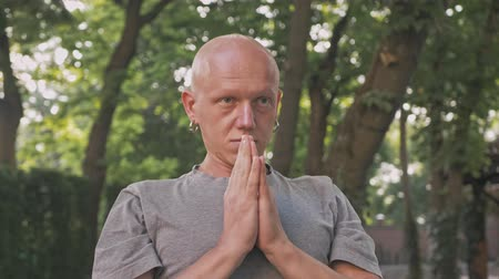 отступление : Concentrated bald man doying yoga with pray gesture in park outdoors