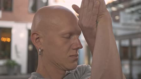 закрытыми глазами : Close up view of concentrated handsome bald man doying yoga exercise with closed eyes in park outdoors