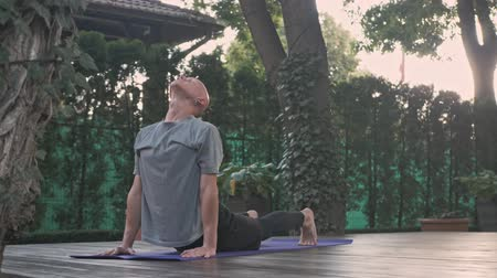 retiro espiritual : Focused bald man doying yoga exercise on mat in park outdoors Archivo de Video