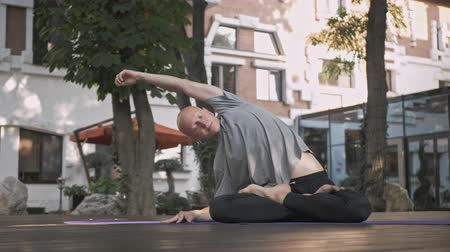retiro espiritual : Pleased handsome bald man doying yoga exercise on mat in park outdoors
