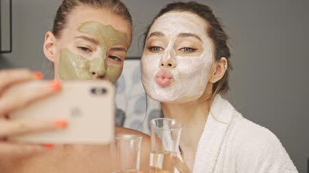 faíscas : Two pretty smiling girls friends with facial mask on their faces making selfie by smartphone at home Stock Footage