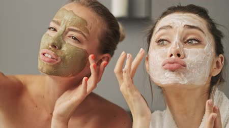enjoys : Two pretty smiling girls friends with facial mask on their faces posing and enjoying the moment at home
