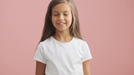 charisma : Happy little girl looking at the camera and smiling over pink background isolated Stock Footage