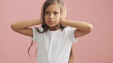 gyerekes : Sad little girl covers ears with her hands and looking around over pink background isolated Stock mozgókép