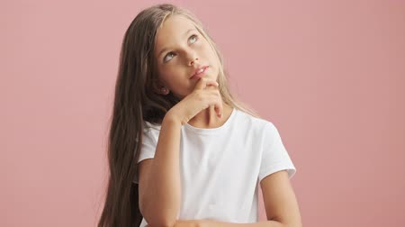 compreensão : Pensive little girl thinking and making idea gesture over pink background isolated Stock Footage