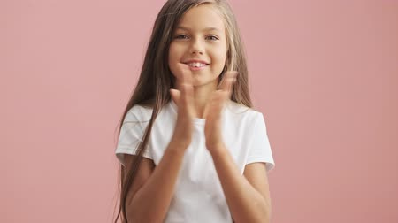 regozijo : Smiling little girl claps and looks at the camera over pink background isolated