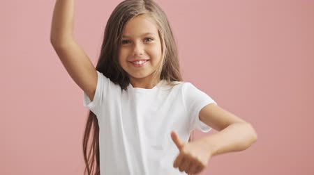 харизматический : Smiling little girl shows thumbs up gesture over pink background isolated