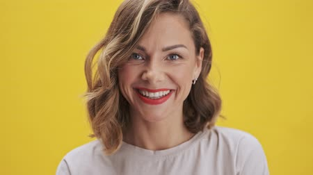 прическа : Charming young woman with red lips laughing to the camera over yellow background isolated Стоковые видеозаписи