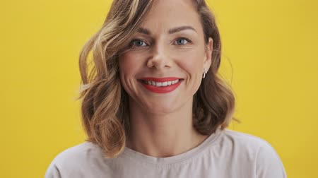 прическа : Happy young woman with red lips smiling to the camera over yellow background isolated