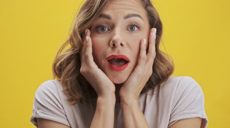 údiv : Positive young woman with red lips shows surprise emotion with touching her cheeks while looking at the camera over yellow background isolated