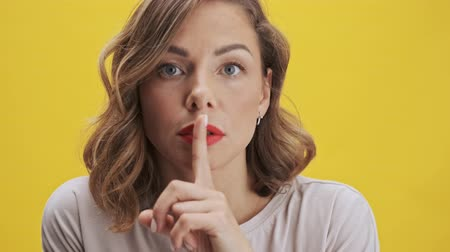 тишина : Goodly young woman with red lips making a silence gesture while looking at the camera over yellow background isolated