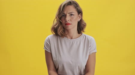 間違った : Beautiful young woman with red lips listen and disagree with something while looking at the camera over yellow background isolated 動画素材