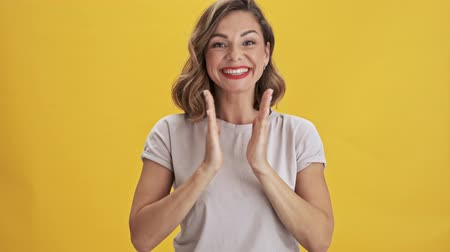 isolar : Beautiful young woman with red lips clap her hands and smiling while looking at the camera over yellow background isolated