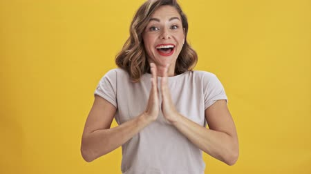 zbraně : Pretty young woman with red lips laughing and applauding while looking at the camera over yellow background isolated
