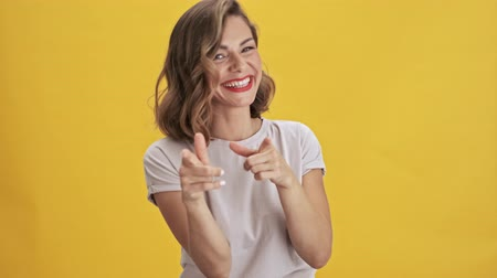 прическа : Beautiful young woman with red lips laughing and pointing her finger to the camera over yellow background isolated