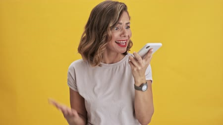 expressing negativity : Confused young woman with red lips expressing outrage and screaming while talking on mobile phone over yellow background isolated