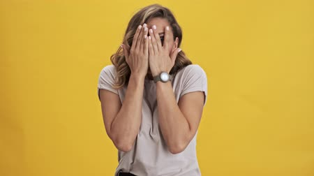 скрывать : Frighten and scared young woman with red lips covers her face with her hands and peeping through her fingers over yellow background isolated