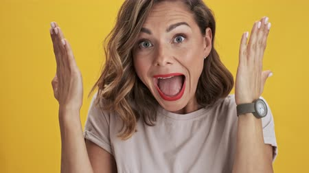 скрывать : Happy and positive young woman with red lips covers her face with her hands and peeping through her fingers over yellow background isolated