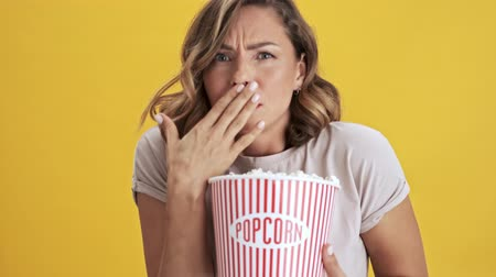 попкорн : Focused young woman with red lips holding a basket of popcorn and showing disgusting while looking at the camera over yellow background isolated