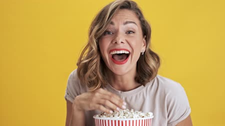 попкорн : Happy young woman with red lips holding a basket of popcorn watching a comedy and laughing over yellow background isolated