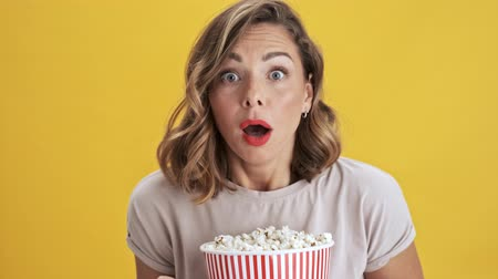 premiere : Focused on wathing a movie young woman with red lips holding a basket of popcorn and showing disgusting and feeling scary while looking at the camera over yellow background isolated