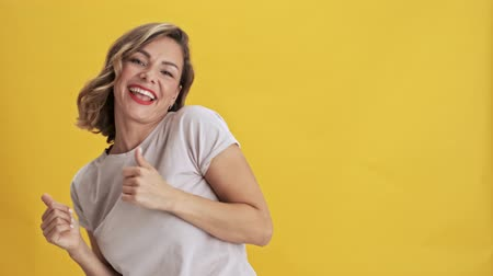 прическа : Charming young woman with red lips dancing with arms folded along the body over yellow background isolated Стоковые видеозаписи