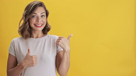 fryzura : Beautiful young woman with red lips smiling and pointing with finger to the side and making thumb up gesture in another while looking at the camera over yellow background isolated