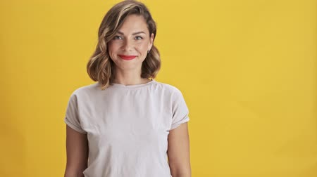 girmek : Beautiful young woman with red lips appears from the side while looking at the camera over yellow background isolated Stok Video